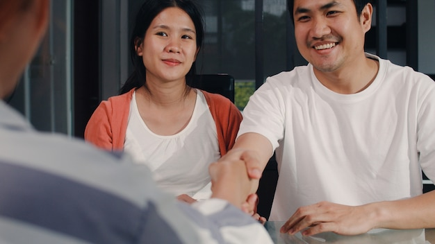 Os pares grávidos asiáticos novos assinam originais do contrato em casa, família japonesa que consulta com o conselheiro financeiro dos bens imobiliários, comprando a casa nova e o aperto de mão com o corretor na sala de visitas na manhã.