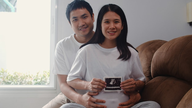 Os pares grávidos asiáticos novos mostram e olhando o bebê da foto do ultrassom na barriga. mamãe e papai se sentindo feliz sorrindo pacífica enquanto cuida criança deitado no sofá na sala de estar em casa.