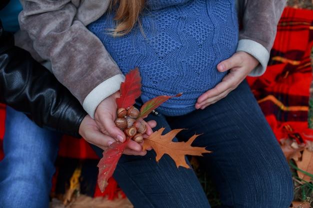 Os pares grávidos felizes andam na natureza no parque do outono.