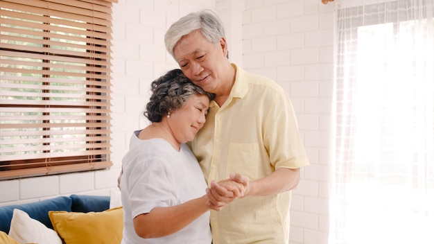 Os pares idosos asiáticos que dançam junto quando escutam a música na sala de visitas em casa, par doce apreciam o momento do amor ao ter o divertimento quando relaxado em casa.