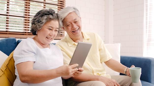 Os pares idosos asiáticos que usam a tabuleta e bebendo o café na sala de visitas em casa, pares apreciam o momento do amor ao encontrar-se no sofá quando relaxado em casa.