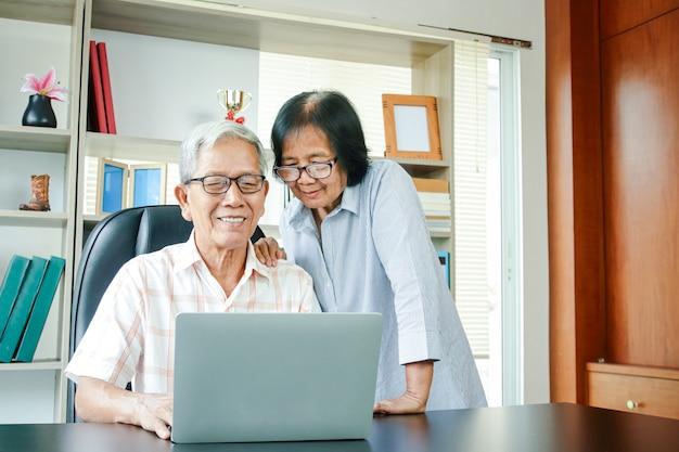 Os pares idosos asiáticos trabalham em casa, felizes na aposentadoria.