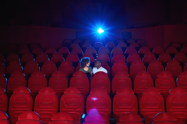 Os pares inter-raciais novos que sentam-se em uma sala de cinema vazia que olha um filme junto copyspace amam o conceito romântico da atividade do entretenimento da data do aniversário do romance vip.