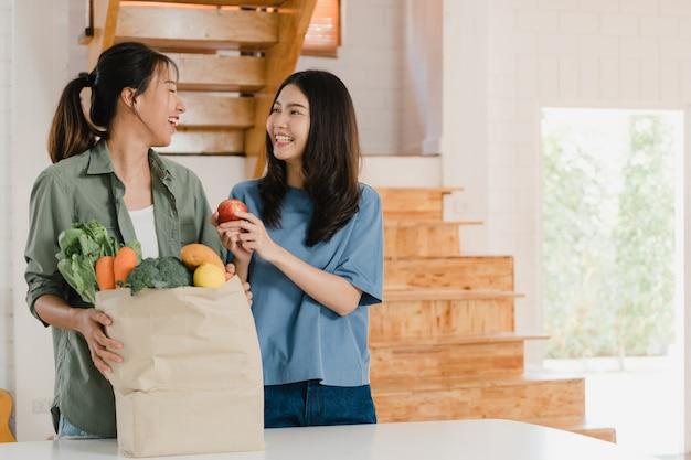 Os pares lésbicas asiáticos das mulheres do lgbtq guardam sacos de papel das compras na mercearia em casa