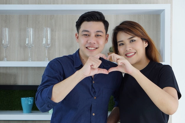 Os pares novos asiáticos que estão próximos um do outro e que fazem uma forma do coração feita com seus dedos chamam o amor no ar