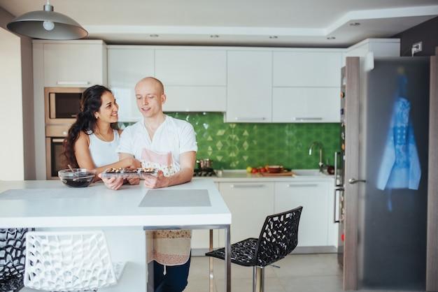 Os pares novos bonitos representaram graficamente o sorriso ao cozinhar na cozinha em casa.