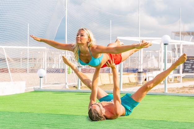 Os pares novos mulher e homens no campo que fazem a ioga da aptidão exercitam junto. elemento acroyoga para força e equilíbrio