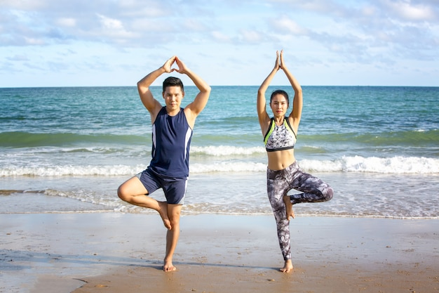 Os pares novos no sportswear que estão e exercitam o corpo na praia na manhã.