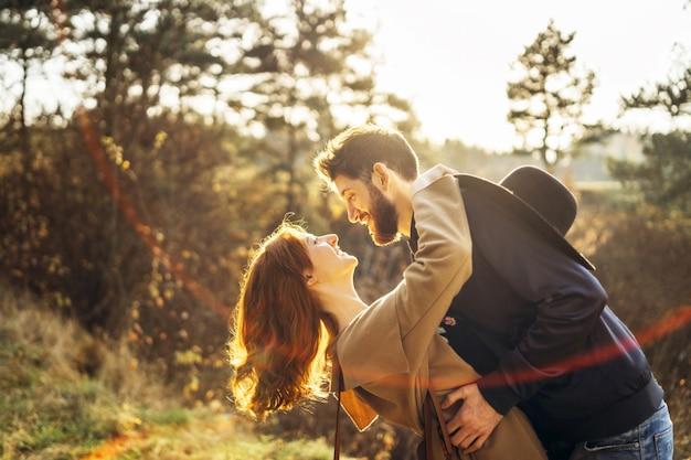 Os pares românticos novos felizes passam o tempo junto ao ar livre.