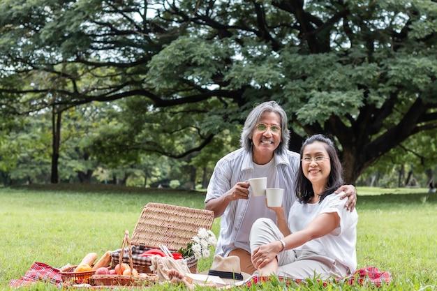 Os pares sênior asiáticos que bebem o café e fazem um piquenique no parque.