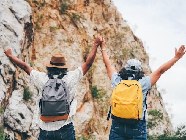 Os pares sênior viajam em umas férias de verão. eles estão de mãos dadas e caminhando juntos.