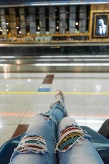 Os passageiros aguardam o voo na área de espera do aeroporto. visão em primeira pessoa, garota de jeans rasgados