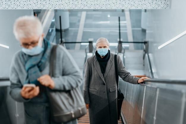 Os passageiros com máscaras de proteção mantêm distância enquanto estão na escada rolante do metrô