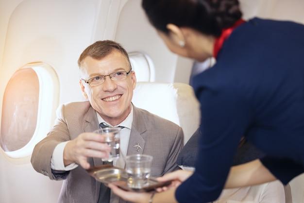 Os passageiros recebem água servida por uma aeromoça no avião, os comissários servem a bordo
