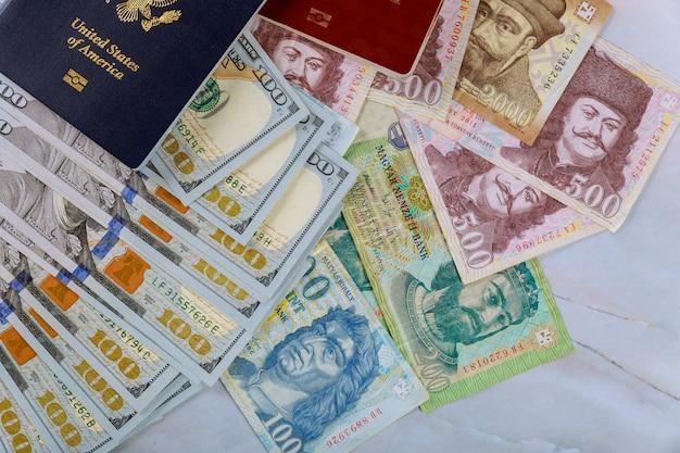 Os passaportes húngaros e passaporte americano com notas de dinheiro american cem dollar dollar e forints em dupla cidadania
