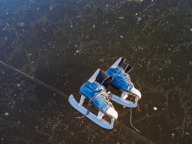 Os patins azuis velhos encontram-se no gelo de um lago congelado no início da manhã ensolarada no inverno