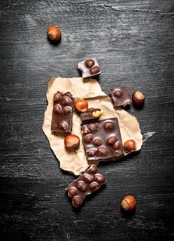 Os pedaços de chocolate com avelãs inteiras. sobre um fundo preto de madeira.