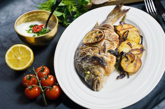 Os peixes cozidos de dorado em uma placa branca, decoram batatas fritadas.