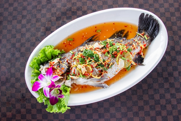 Os peixes cozinhados do robalo com limão puseram um prato cerâmico branco no assoalho de couro o teste padrão de grade. vista do topo.