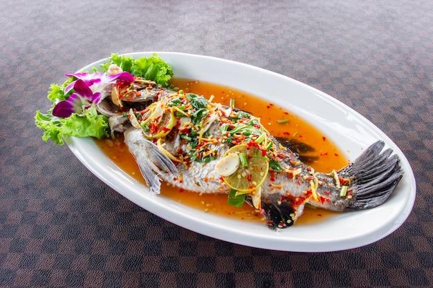 Os peixes cozinhados do robalo com limão puseram um prato cerâmico branco no assoalho de couro o teste padrão de grade.