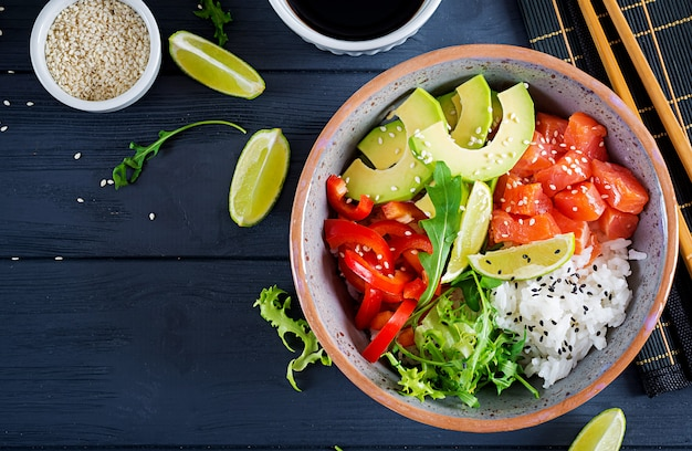 Os peixes salmon havaianos puxam a bacia com arroz, abacate, paprika, sementes de sésamo e cal.