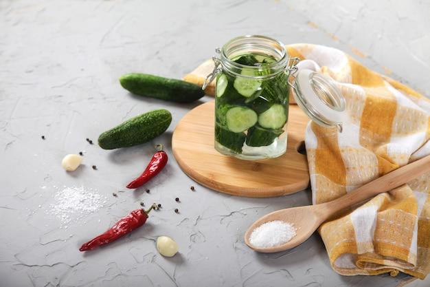 Os pepinos fermentados cortados em um frasco de vidro estão em uma placa de madeira.