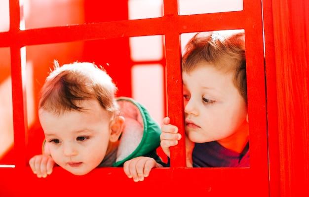 Os pequenos meninos estão perto da parede vermelha