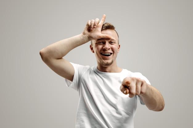 Os perdedores vão para casa. retrato de cara feliz mostrando sinal de perdedor na testa e sorrindo em causa da vitória e rindo sobre fundo cinza