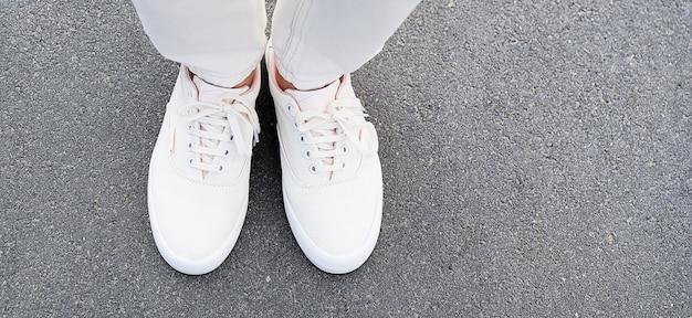 Os pés da garota de jeans branco e tênis na calçada.