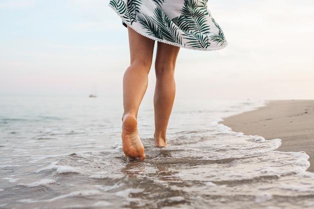 Os pés da mulher caminham lentamente e relaxam na praia tropical de areia com fundo de céu azul. conceito de férias e férias.