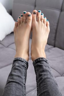 Os pés da mulher em jeans com pedicure no sofá cinza em casa. design de unhas turquesa lindo de verão
