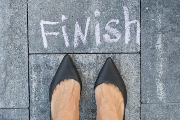 Os pés da mulher em sapatos pretos clássicos antes da palavra terminar