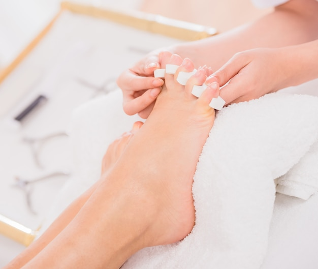 Os pés da mulher em separadores do dedo do pé do pedicure no salão de beleza do prego.