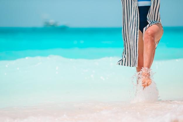 Os pés da mulher na praia de areia branca em águas rasas