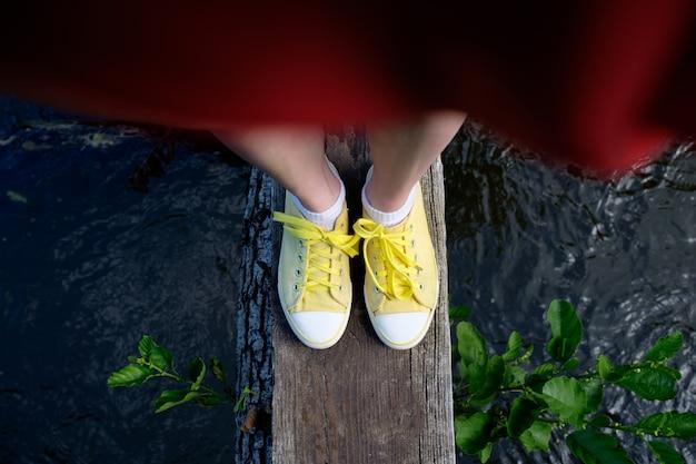 Os pés da mulher nas sapatilhas amarelas que estão no tronco sobre o rio, close-up