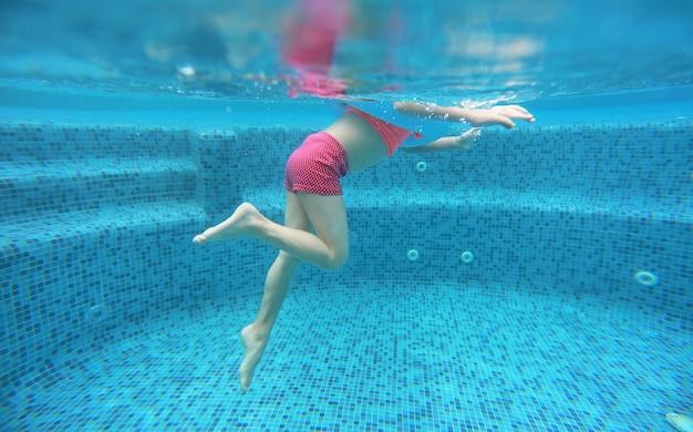 Os pés da opinião da menina da criança de debaixo da água.