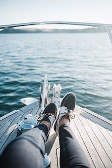 Os pés da pessoa no barco navegando no mar durante o dia