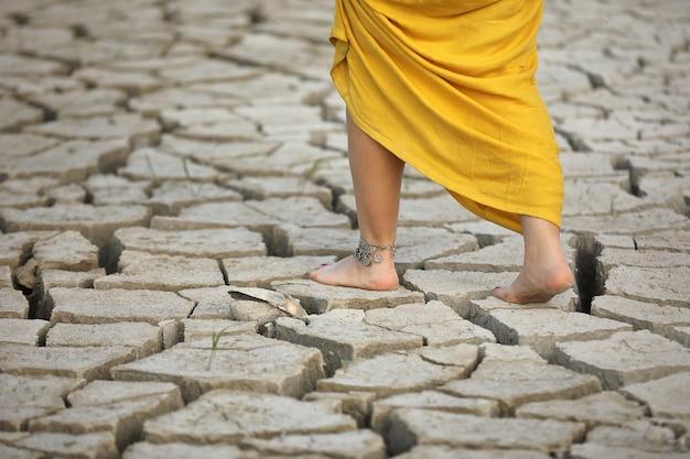Os pés das mulheres caminham no solo seco.