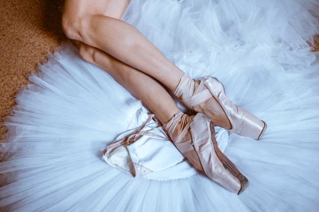 Os pés de close-up de jovem bailarina em sapatilhas