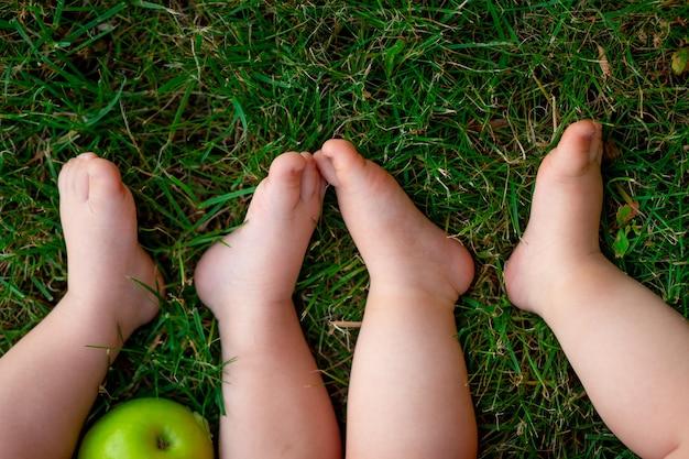 Os pés de dois bebês na grama verde, espaço para texto