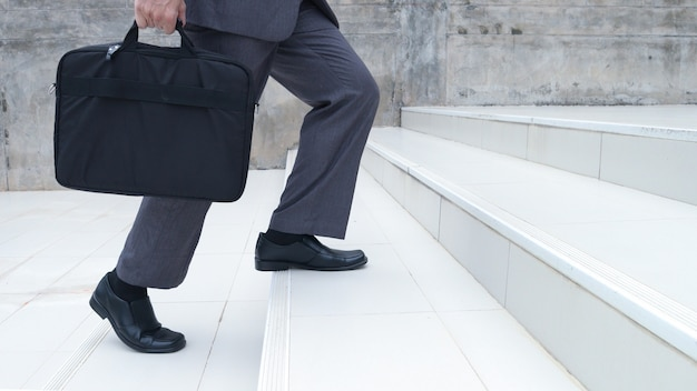 Os pés de um homem de negócios. carregando uma mala na mão, subindo as escadas para trabalhar na empresa. estilo de vida das pessoas bem sucedido e conceito de concorrência