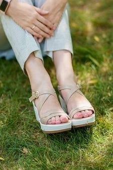 Os pés de uma mulher em sapatos de verão e calças despojadas em pé na grama verde