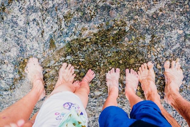 Os pés descalços de uma família resfriados na água de um riacho, conectando-se à natureza, longe de tudo.