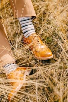 Os pés do noivo com calças marrons, meias listradas e sapatos marrons repousam na grama seca