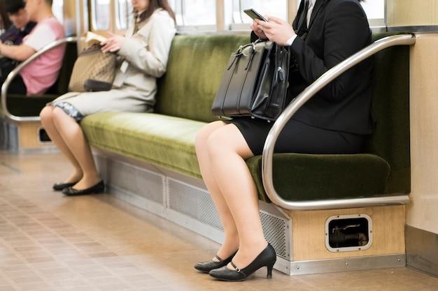 Os pés dos povos vêem na vista à terra do viajante de bilhete mensal do metro de tóquio, seção baixa de passageiros dos transportes públicos.