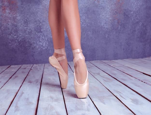 Os pés em close da jovem bailarina em sapatilhas de ponta contra o fundo do chão de madeira