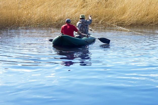Os pescadores da vila no rio colocam a rede.