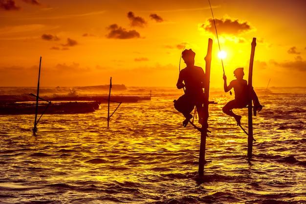 Os pescadores de palafitas no pôr do sol