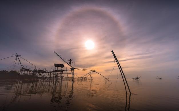 Os pescadores estão pescando cedo no lago.