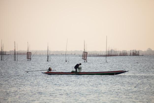 Os pescadores estão pescando no lago.